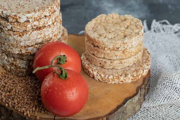 Pila di pane croccante, pomodori e grano saraceno crudo sul pezzo di legno