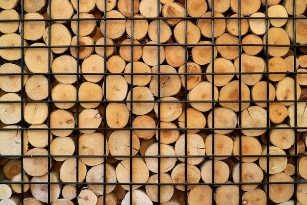 Stack of cut log woods in a metal cage for background or banner