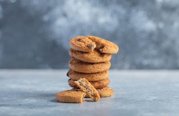 Pila di deliziosi biscotti con scaglie di cioccolato su fondo di marmo