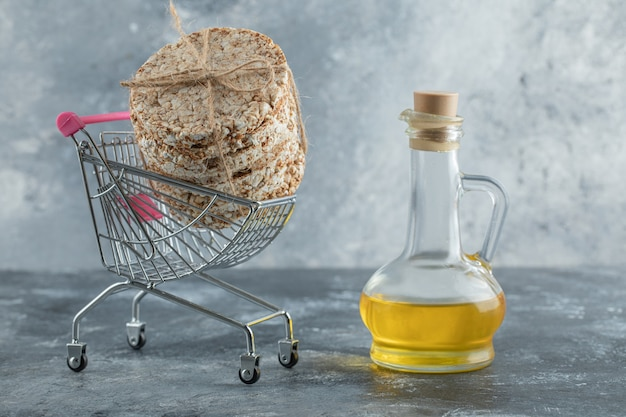 Stack of delicious crispbread in small shopping cart with olive oil