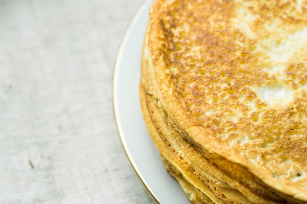 Stack of delicious golden crepes on white plate, on linen cloth background, top view, breakfast