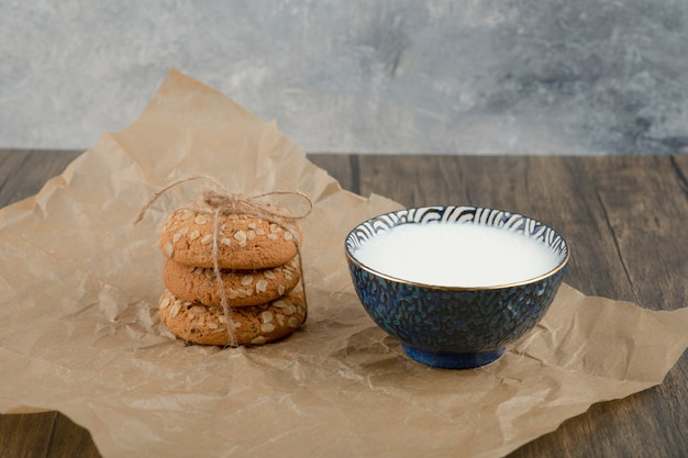 Stack of delicious oatmeal cookies and bowl of fresh milk on wooden surface.
