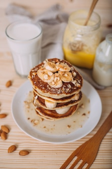 Stack of delicious pancakes with honey, nuts and slices of banana.