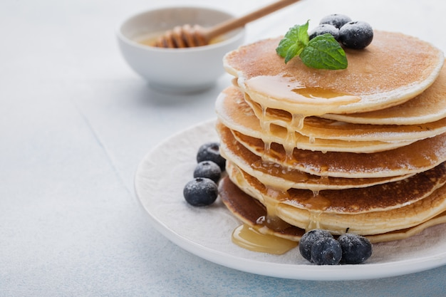 A stack of delicious pancakes with honey.
