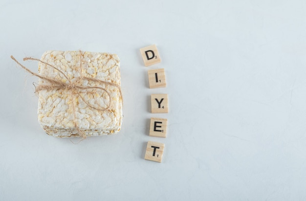 Stack of delicious puffed crispbread tied with rope and wooden letters.