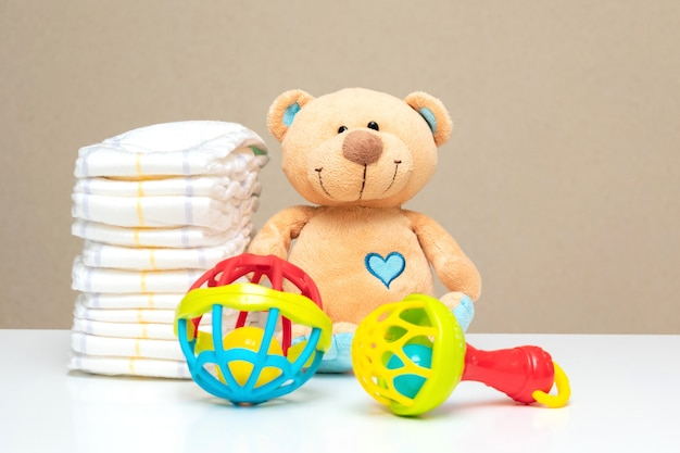 Stack of diapers, cute teddy bear with toys on table-set for baby shower with copy space.
