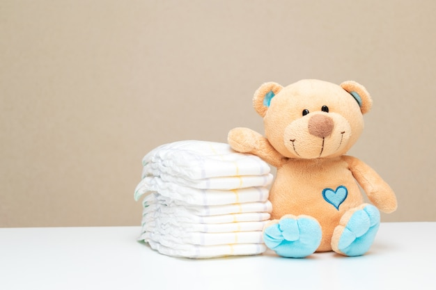 Stack of diapers with toy teddy bear on table