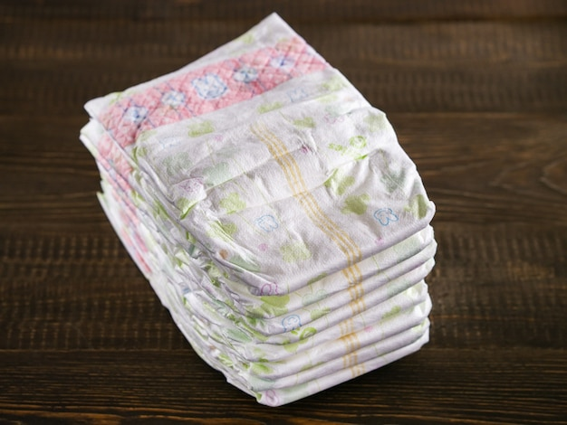 Stack of diapers on wooded background