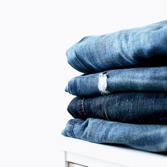 Stack of different blue denim jeans trousers on the shelf or table. photo of stacked various shade jeans close up on white background with copy space for text design. canvas denim fashion texture.