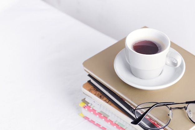Stack of different books and notepads with woman's glasses and coffee cup on the top on a white table.