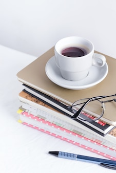 Stack of different books and notepads with woman's glasses and coffee cup on the top on a white table
