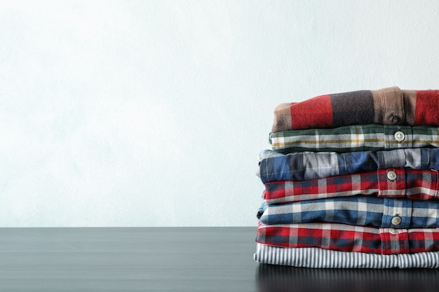 Stack of different shirts on black table