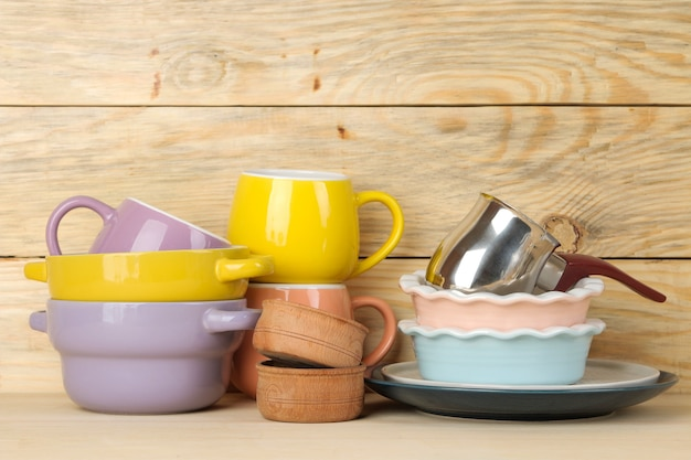 A stack of dishes. colored dishes on a natural wooden table. multi-colored cups and bowls.