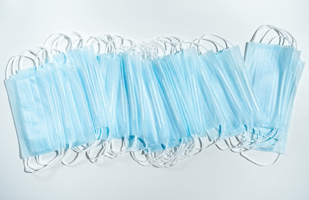 Stack of disposable medical masks on a blue background. face mask for protection virus, flu, coronavirus, covid-19. medical equipment. pharmaceutical background.