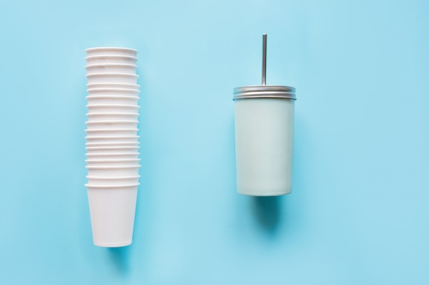 Stack of disposable white cups weekly use and counterweight reusable mug for drinks daily use on blue