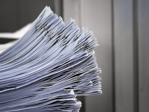 The stack of documents placed on the desk.