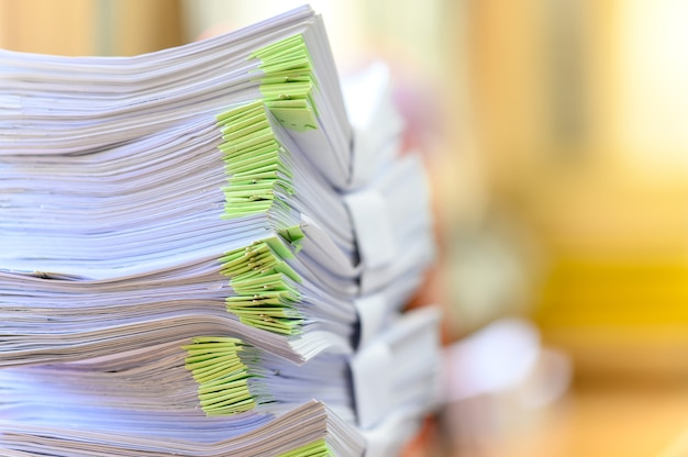 Stack of documents on wooden desk in office
