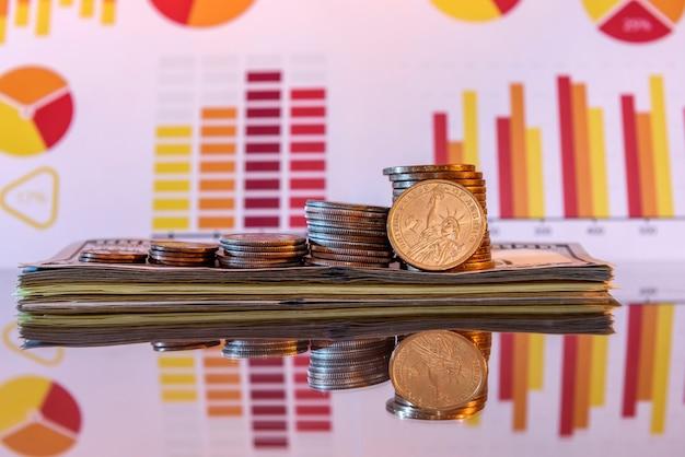 광택있는 표면에 달러와 동전 스택