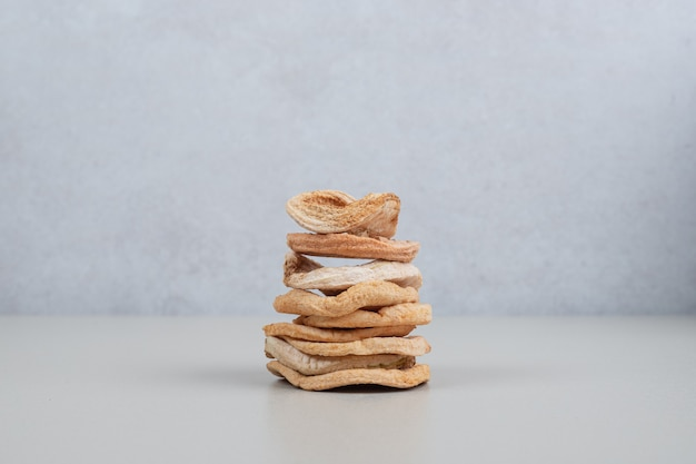 Stack of dried apple chips on white surface