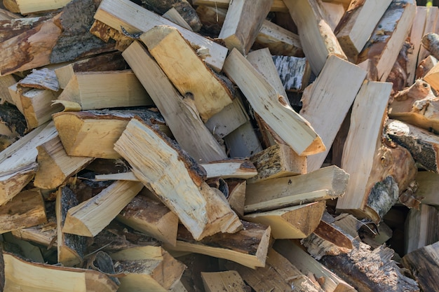 A stack of dry firewood, prepared for winter for heating the house.
