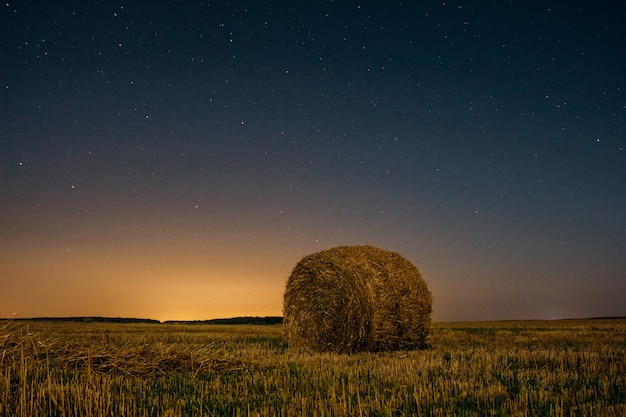 Stack dry hay under the night sky with stars background