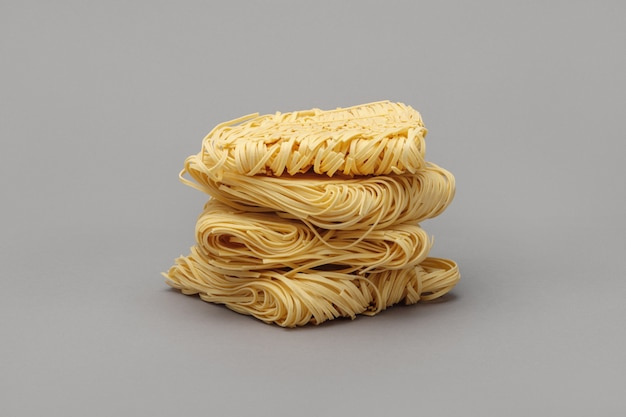 Stack of dry strips of egg noodles (pasta nests) on gray surface.