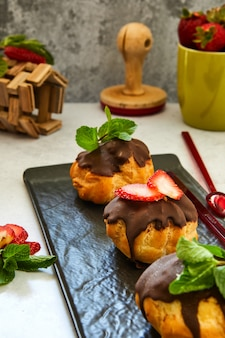 Stack eclair of profiteroles with dark melted chocolate on a black dish.