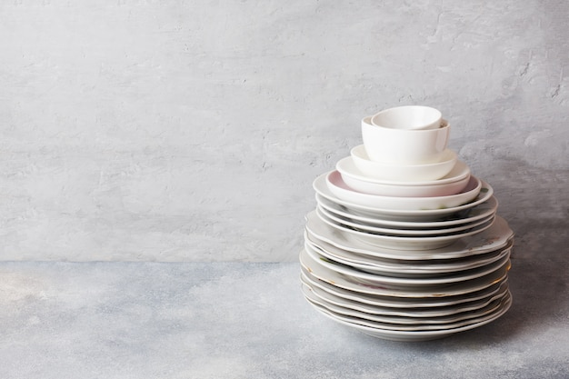 Stack of empty clean plates on a gray table with copy space.