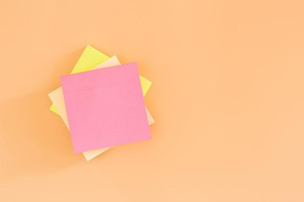 주황색 배경에 빈 스티커 포스트 메모 용지를 쌓습니다. 그것을 종이 메모를 게시합니다. 프리미엄 사진