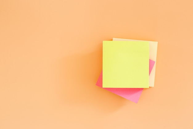 주황색 배경에 빈 스티커 포스트 메모 용지를 쌓습니다. 그것을 종이 메모를 게시합니다.