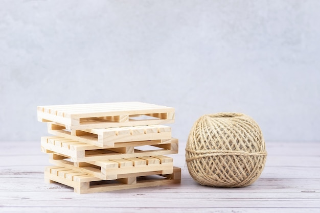 A stack of empty wooden pallets and a rope on a gray surface