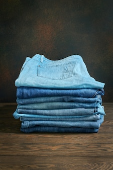 Stack of fancy blue jeans on a wooden table with copy space