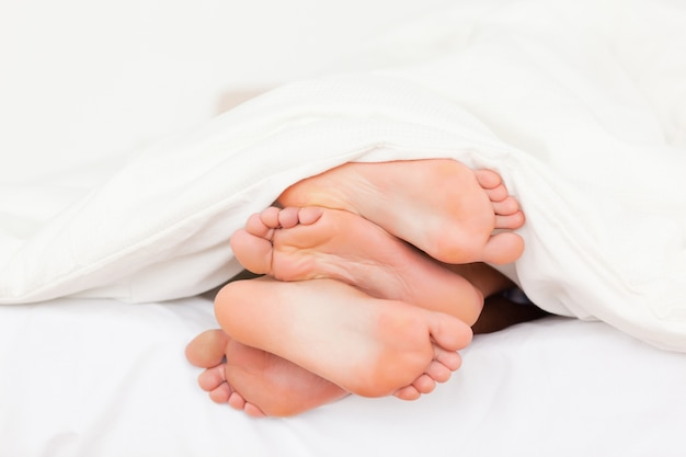 Stack of feet in a bed