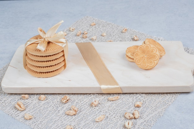 Stack of festive biscuits and peanuts on wooden board. high quality photo