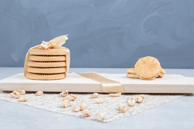 Stack of festive biscuits and peanuts on wooden board.