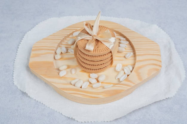 Stack of festive biscuits and peanuts on wooden plate. high quality photo