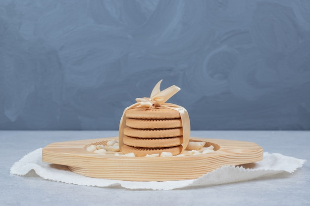 Stack of festive biscuits and peanuts on wooden plate.