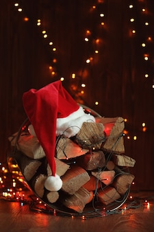 Stack of firewood, garland and santa claus hat on wooden surface