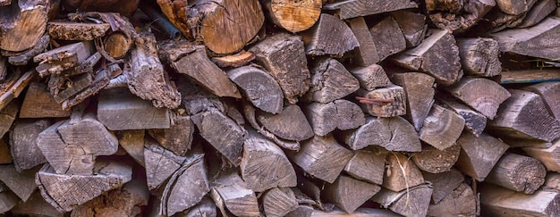 Stack of firewood stacked for a stove and a fireplace near the house in rustic rustic style background with space for text