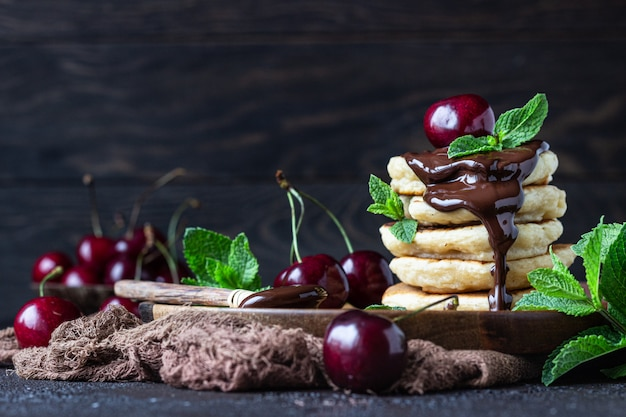 Stack of fluffy pancakes or fritters with chocolate and cherry jam, fresh cherry and mint.