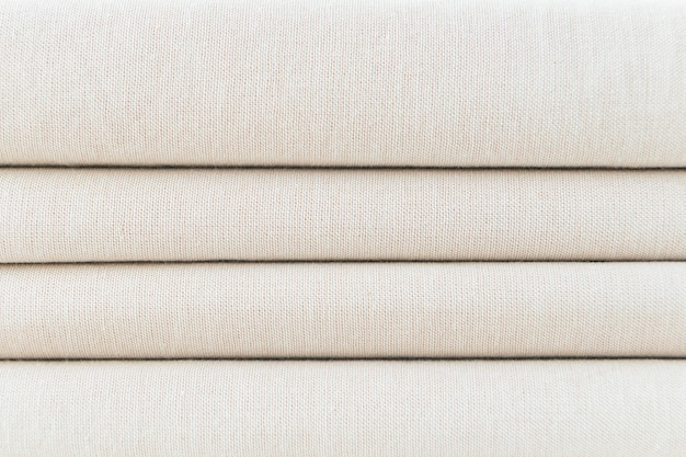 Stack of folded beige woven fabric background