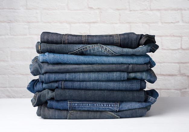 Stack of folded blue jeans against white brick wall