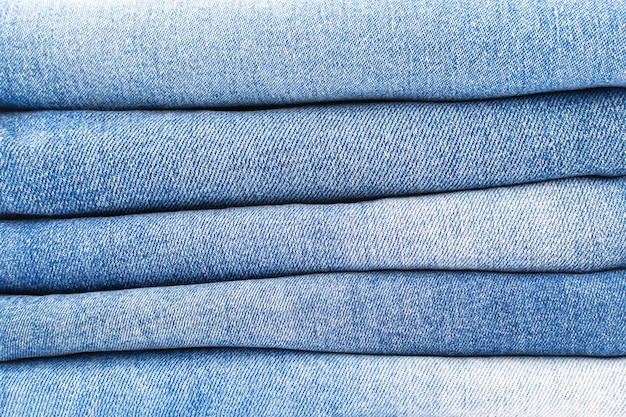 A stack of folded blue jeans closeup denim texture background, a variety of comfortable casual pants and clothing