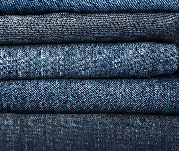 Stack of folded blue jeans pants, full frame