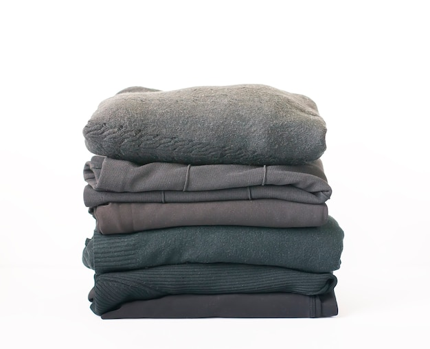 Stack of folded colorful clothes on white background.