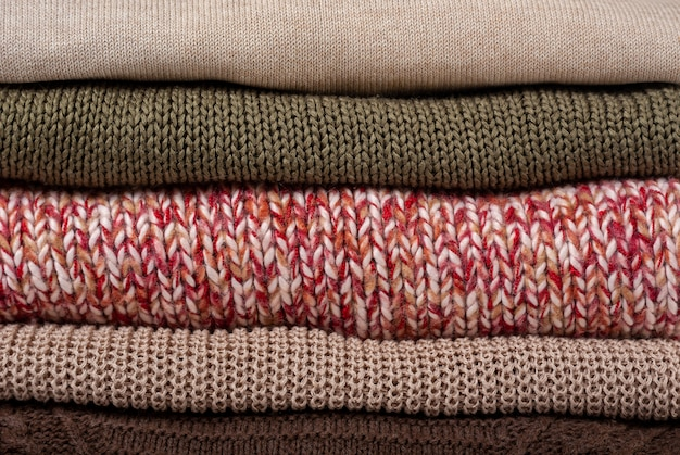 Stack folded colorful knitted sweaters background close up