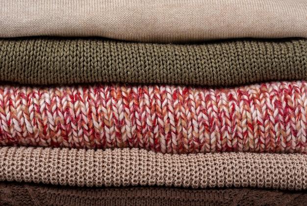 スタック折り畳まれたカラフルなニットセーターの背景をクローズアップ