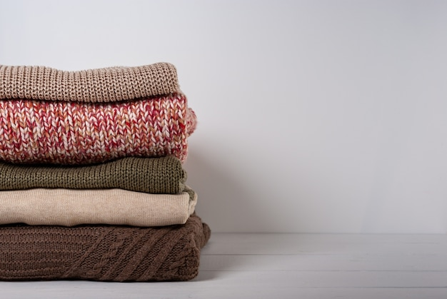 Stack folded colorful knitted sweaters on white wooden background