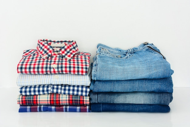 Stack of folded colorful plaid shirts and jeans on white background