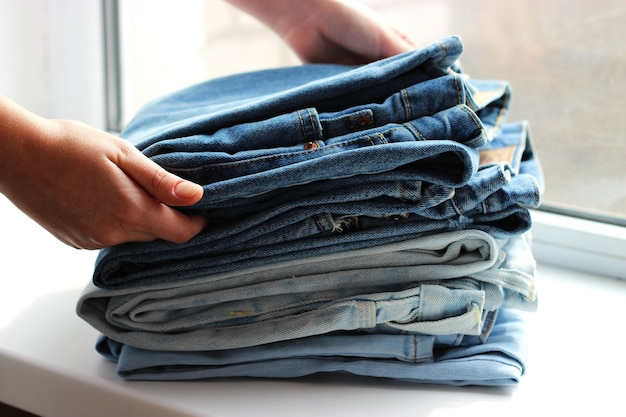Stack of folded jeans in man hands